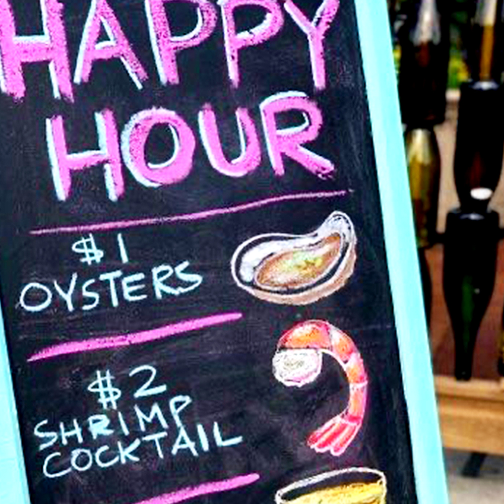 Chalkboard sign on a sidewalk that says happy hour with menu offerings.