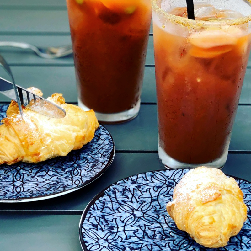 Croissants and Bloody Marys on a tabletop.