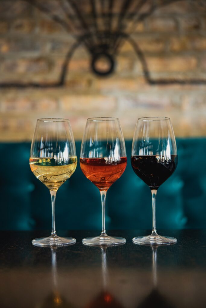 Three wine glasses in a row, one red, one rose and one white wine.